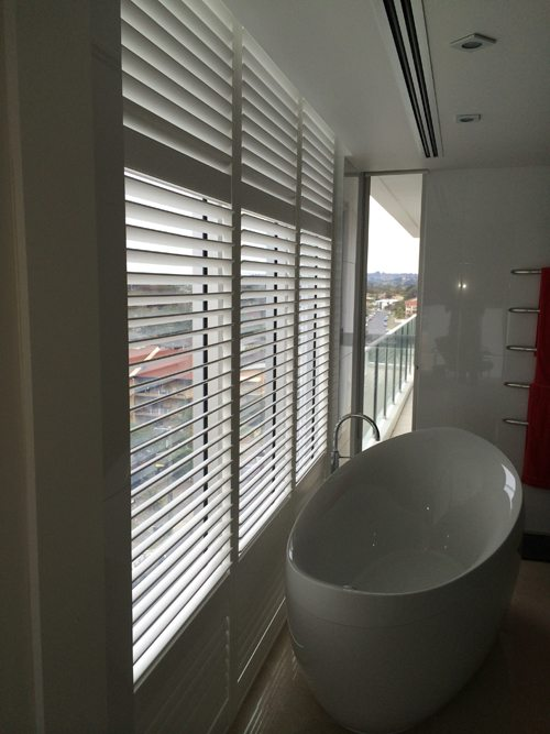 White window shutters installed inside in the bathroom with white bath tub