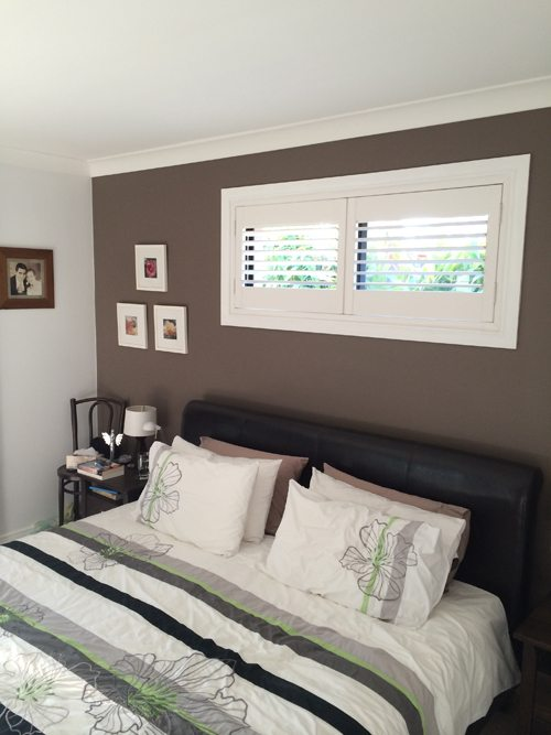 Interior view of bedroom with shutter clifton above bed