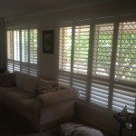 Modern living room with open pane white shutter windows