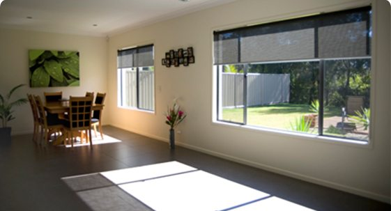 Interior view of living room with wooden dining table and black window blinds