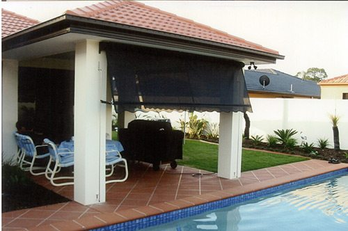 Half open black automatic awnings installed on a roof beside pool area