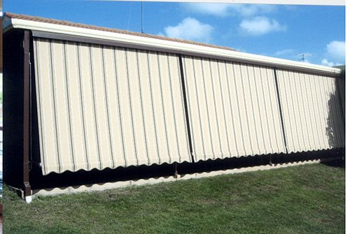 Closed striped automatic awnings in a lawn area