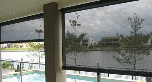 Transparent black window roller installed in a balcony beside a swimming pool