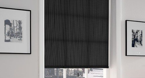 Black roller blinds installed inside black and white living room interior