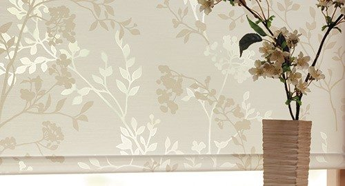 Flower textured roller blinds installed behind beautiful flower pot and vase kept on a table