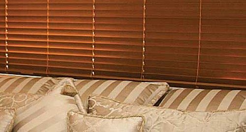Brown venetian timber blinds installed in a window behind a sofa set