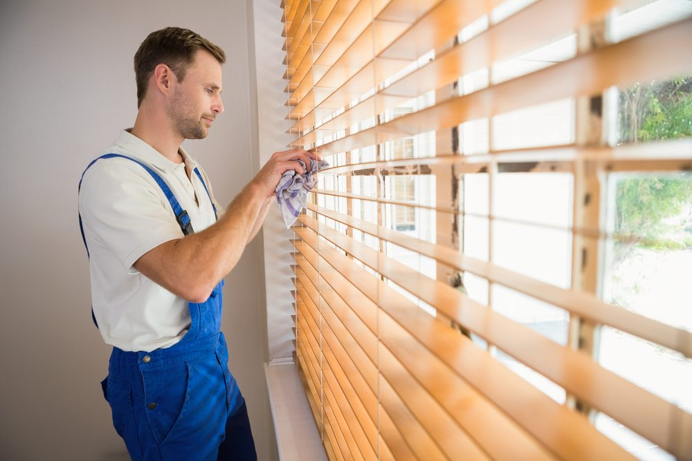 Man cleaning venetian blinds
