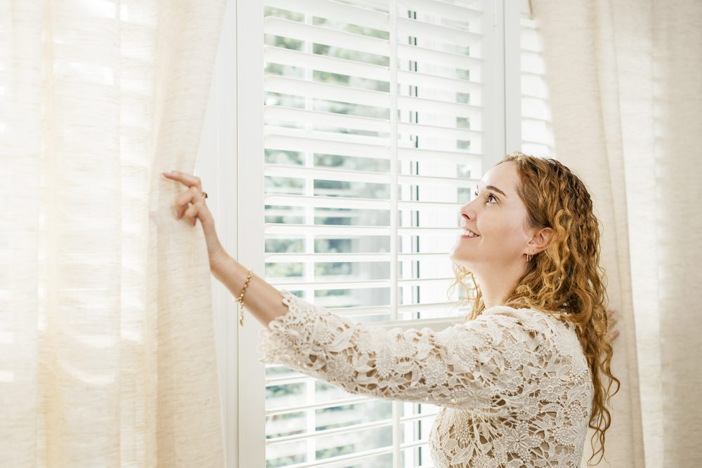 Woman looking out sunny window, pulling back white curtains to reveal white blinds