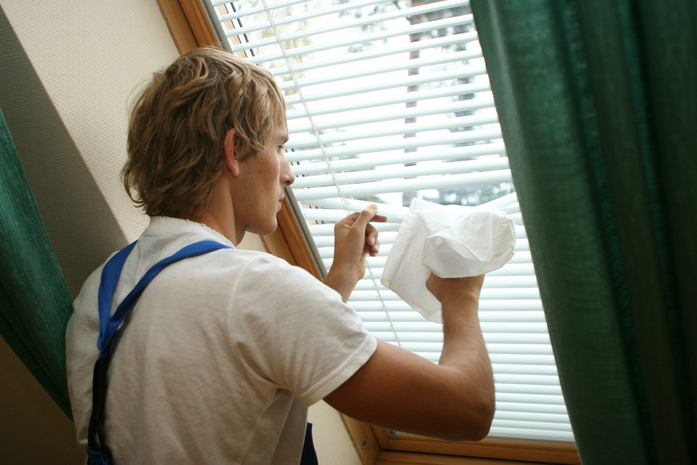 Man in overalls cleans PVC venetian blinds with microfibre cloth