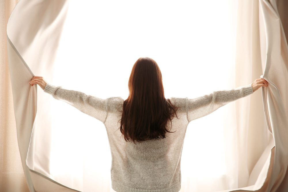 Woman with brown hair opens cream curtains with light shining through