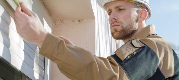 Handyman fits external blinds onto a window