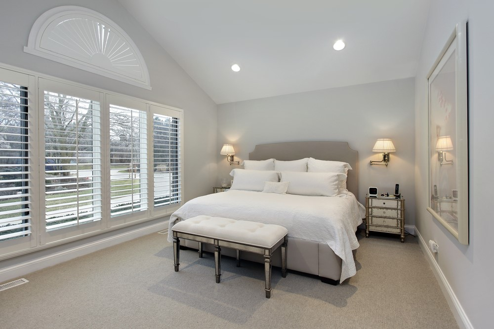 Master bedroom in suburban home with wall of windows